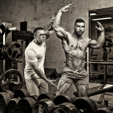Bodybuilder guided by his trainer for correct posing.