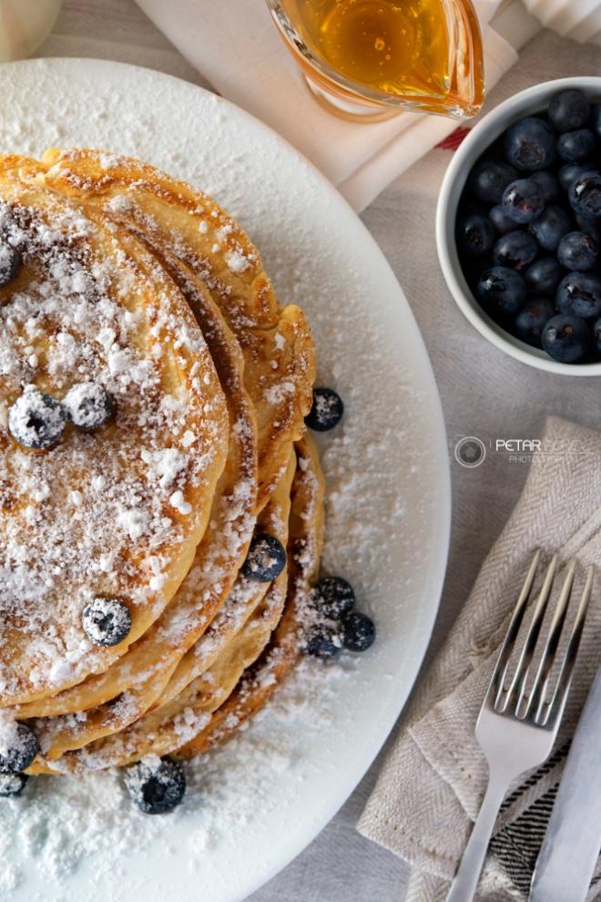 Tasty breakfast of pancakes with blueberries, powdered sugar, milk and honey