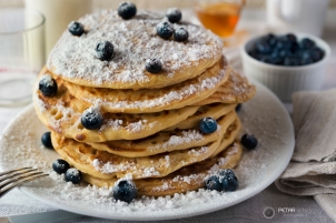 Tasty breakfast of pancakes with blueberries, powdered sugar, milk and honey
