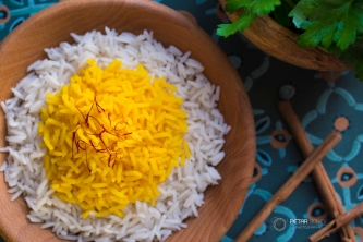 Rice cooked with saffron in a wooden bowl with fresh parsley for garnish